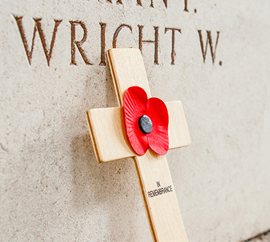 A small wooden cross has a poppy in the middle and is leaning against a Rememberance Day wall of names of people who died in the war.
