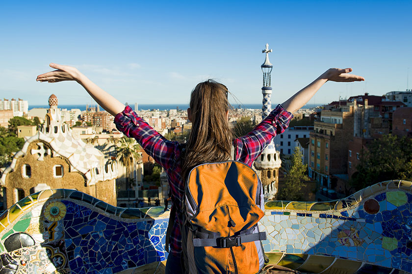 Girl with arms up overlooking Spanish city